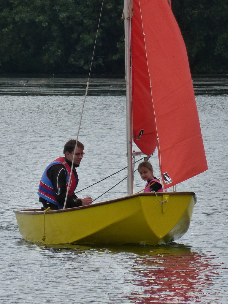 A yellow Mirror dinghy sailing in a light wind