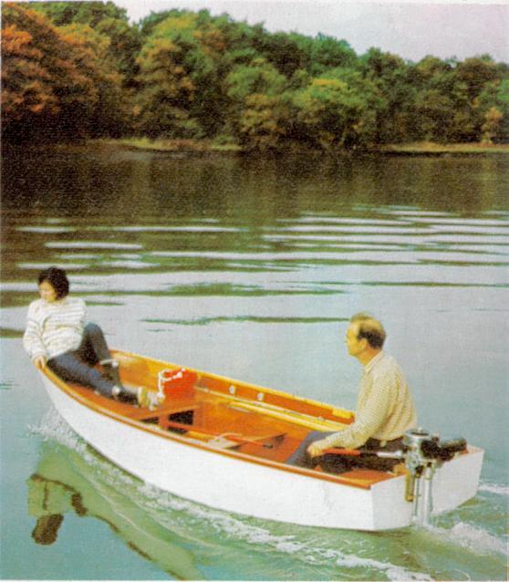 A white Mirror dinghy been propelled by an outboard