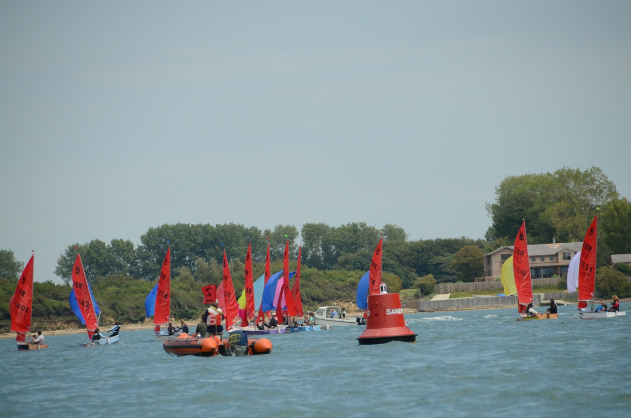 A fleet of Mirror dinghies racing near a red navigation buoy
