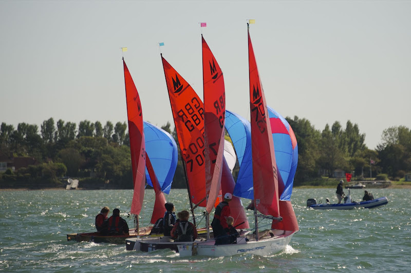 Four Mirror dinghies racing in close company with spinnakers flying