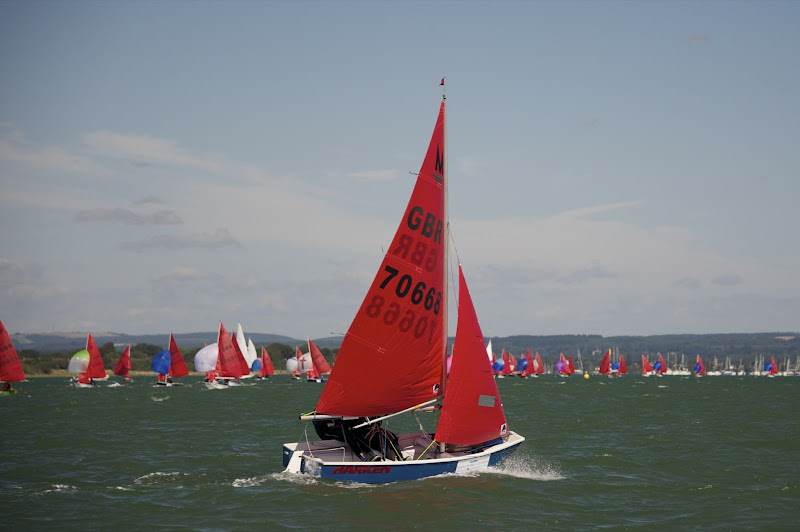 A Mirror racing to windward with competitors running downwind in the background