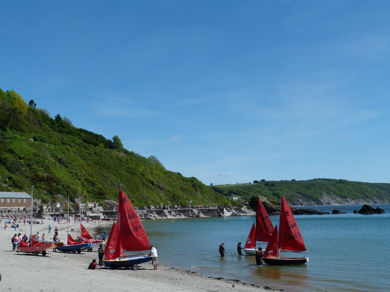 Mirror dinghies launching off a sandy beach into a blue sea under a cloudless blue sky