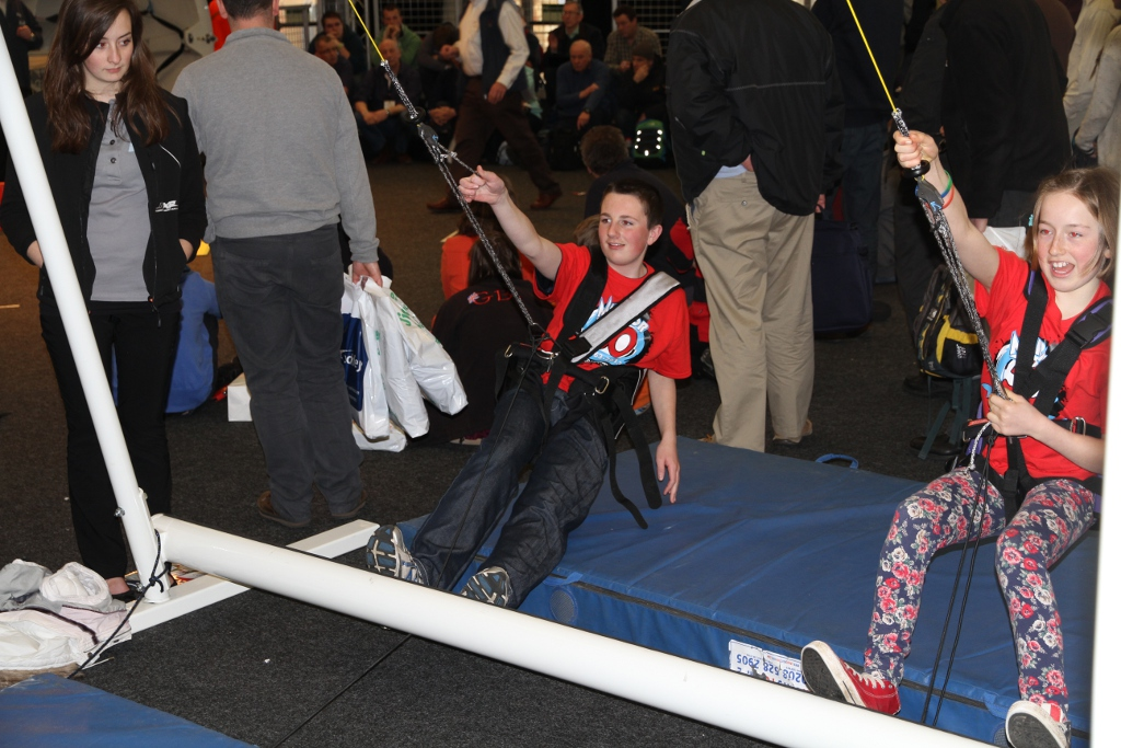 A boy and a girl trying a trapeze simulator
