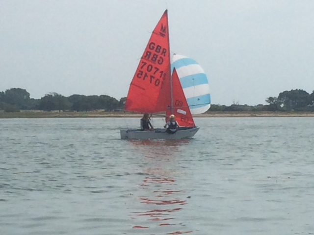 White GRP Mirror dinghy with spinnaker hoisted racing in a light wind