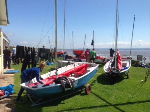 Mirror dinghies being de-rigged on a lawn on a sunny day with wet clothing hung to dry