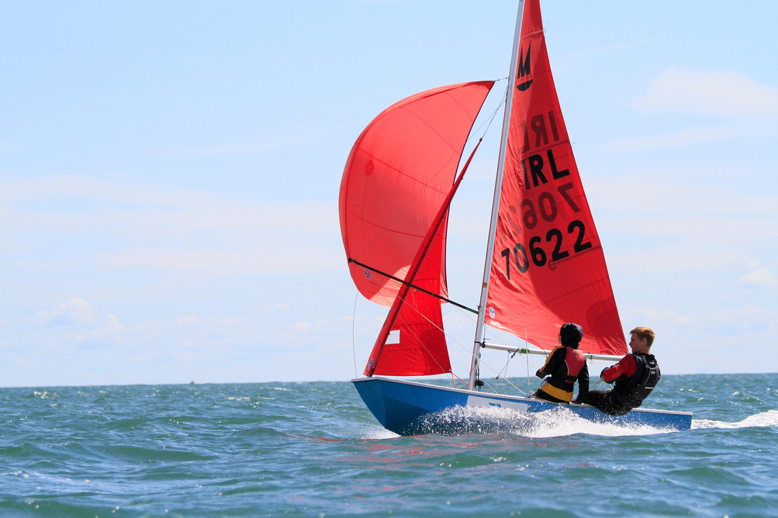 A blue Mirror dinghy with a red spinnaker planning over a blue sea on a sunny day