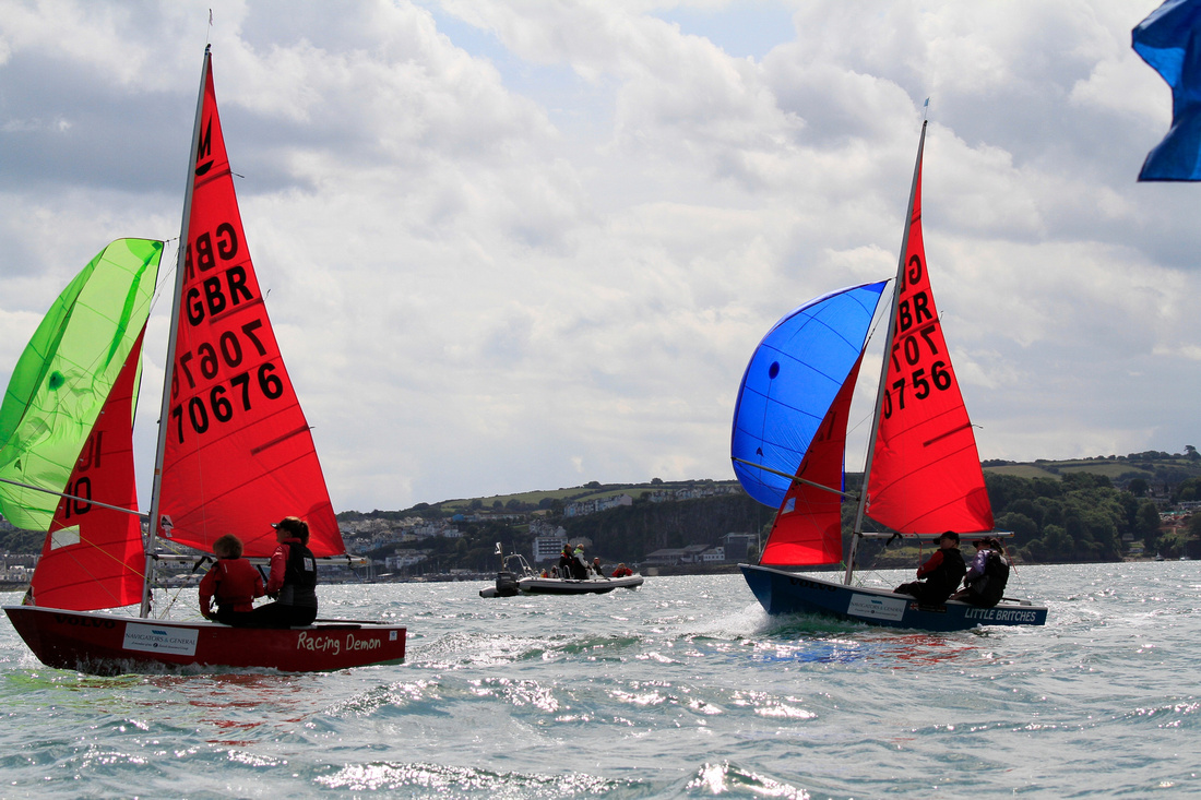 A red Mirror dinghy with green spinnaker crossing the finish line ahead of a blue Mirror dinghy with blue spinnaker