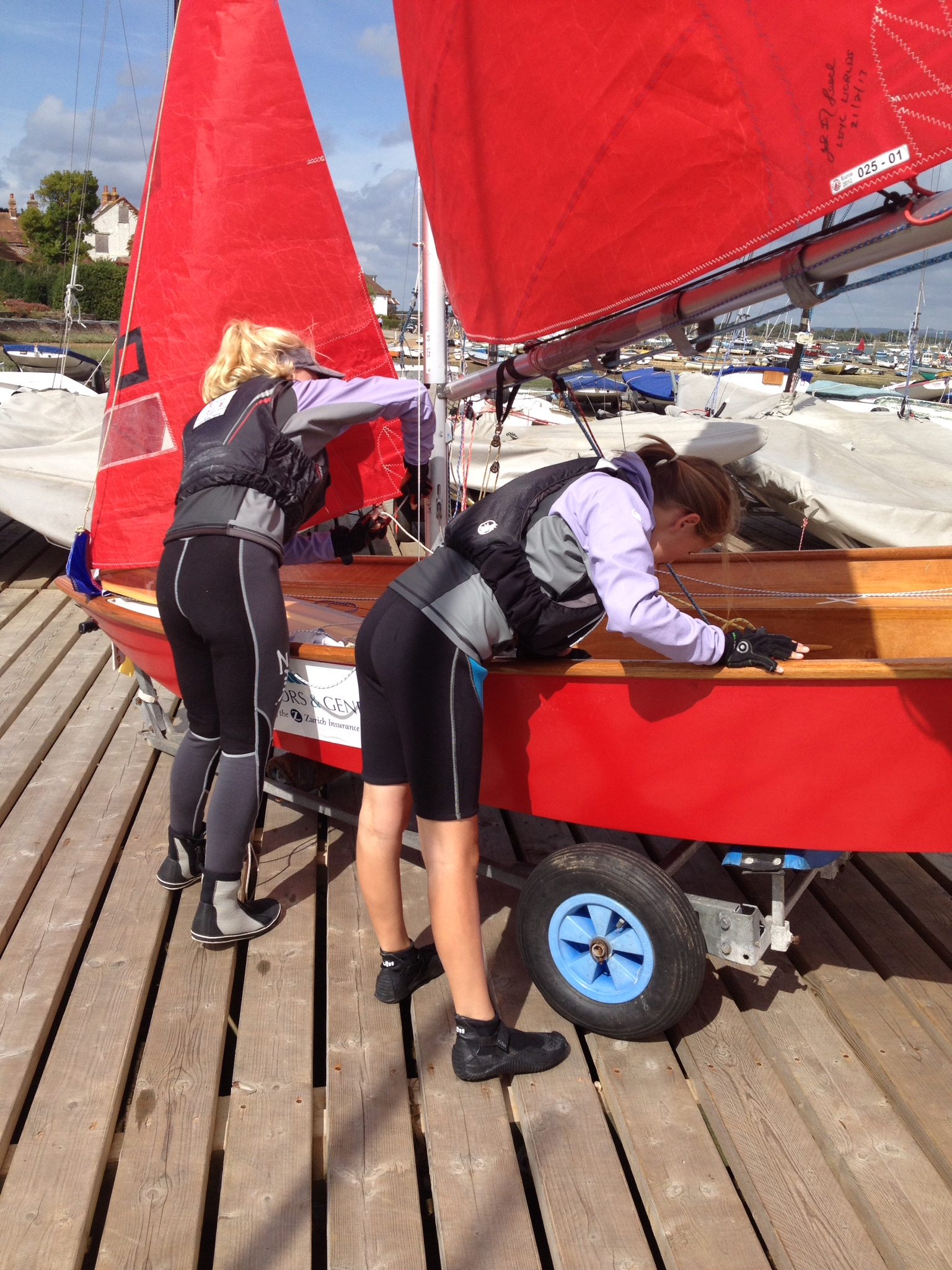 two girls getting a red Mirror dinghy ready to race