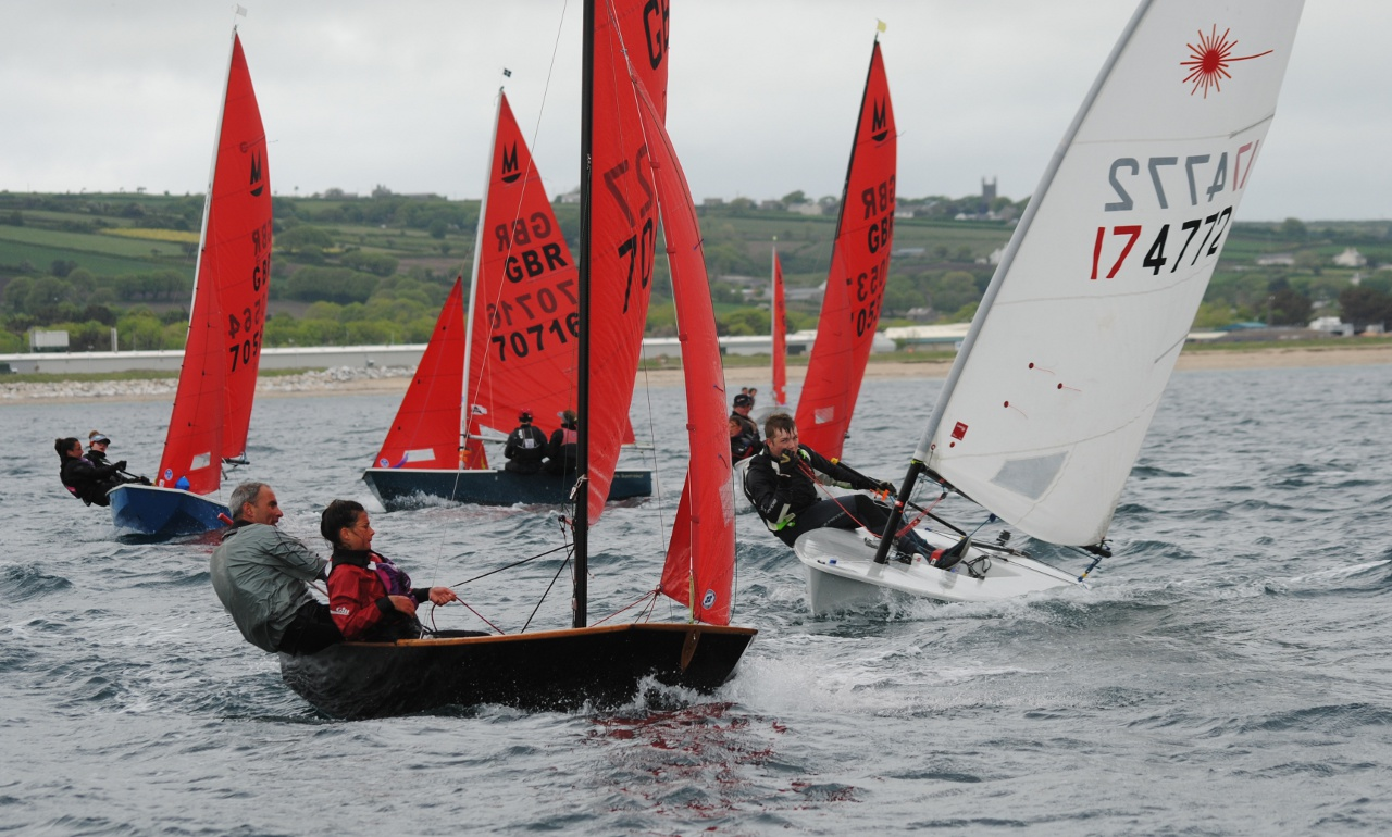 Mirror dinghies and a Laser dinghy racing towards the windward mark