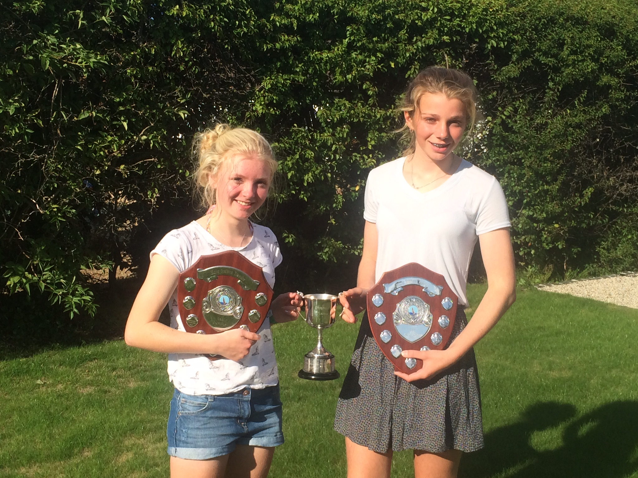 Two girls holding their trophies - a cup and two shields