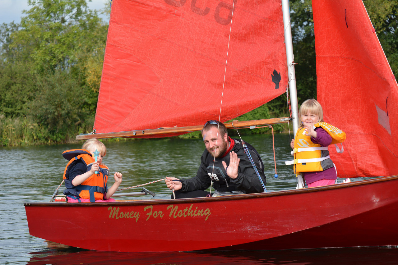 A red Mirror dinghy racing with two children crewing