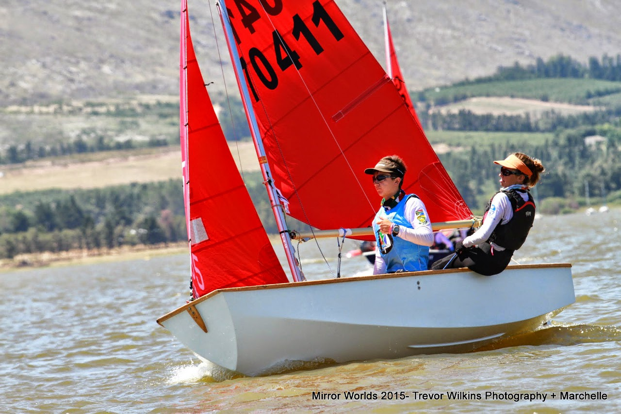 A white wooden Mirror dinghy being sailed to windward