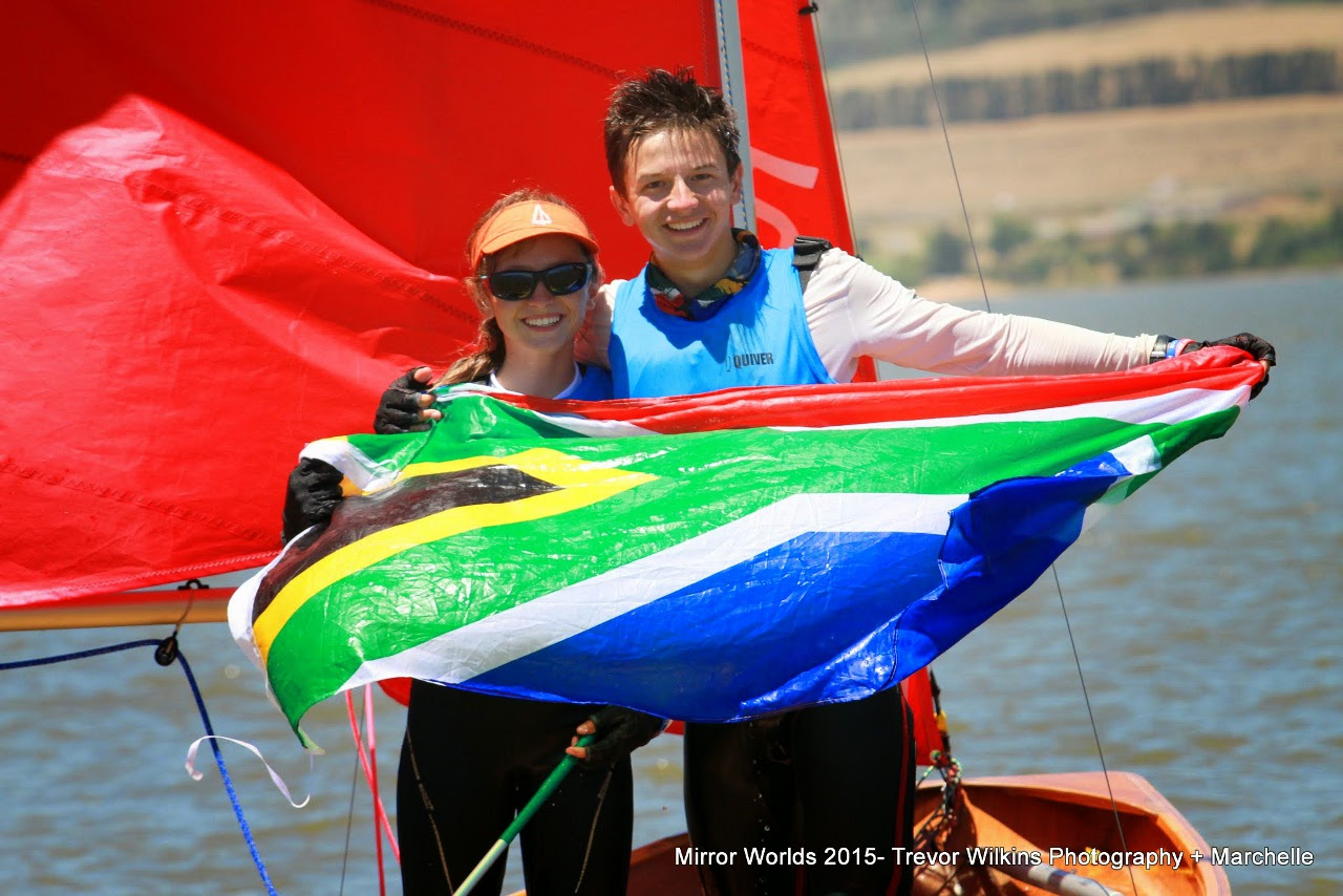 A girl & her brother holding the South African Flag while sitting in their dinghy
