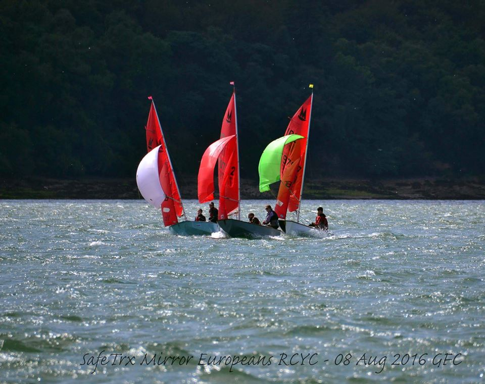 Mirror dinghies racing with spinnakers hoisted on a gusty day