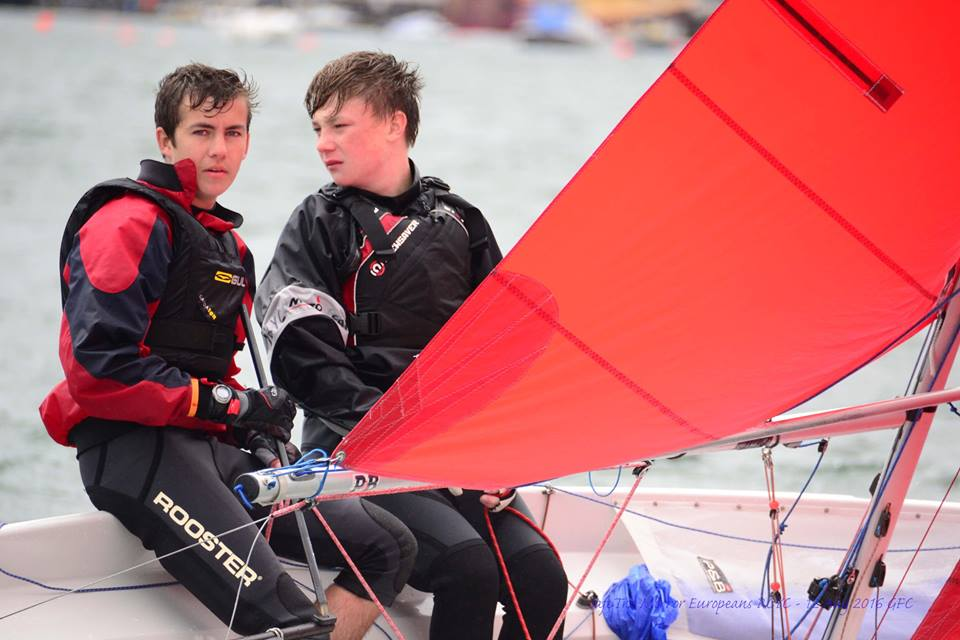 Two teenagers sailing a GRP Mirror heeled over