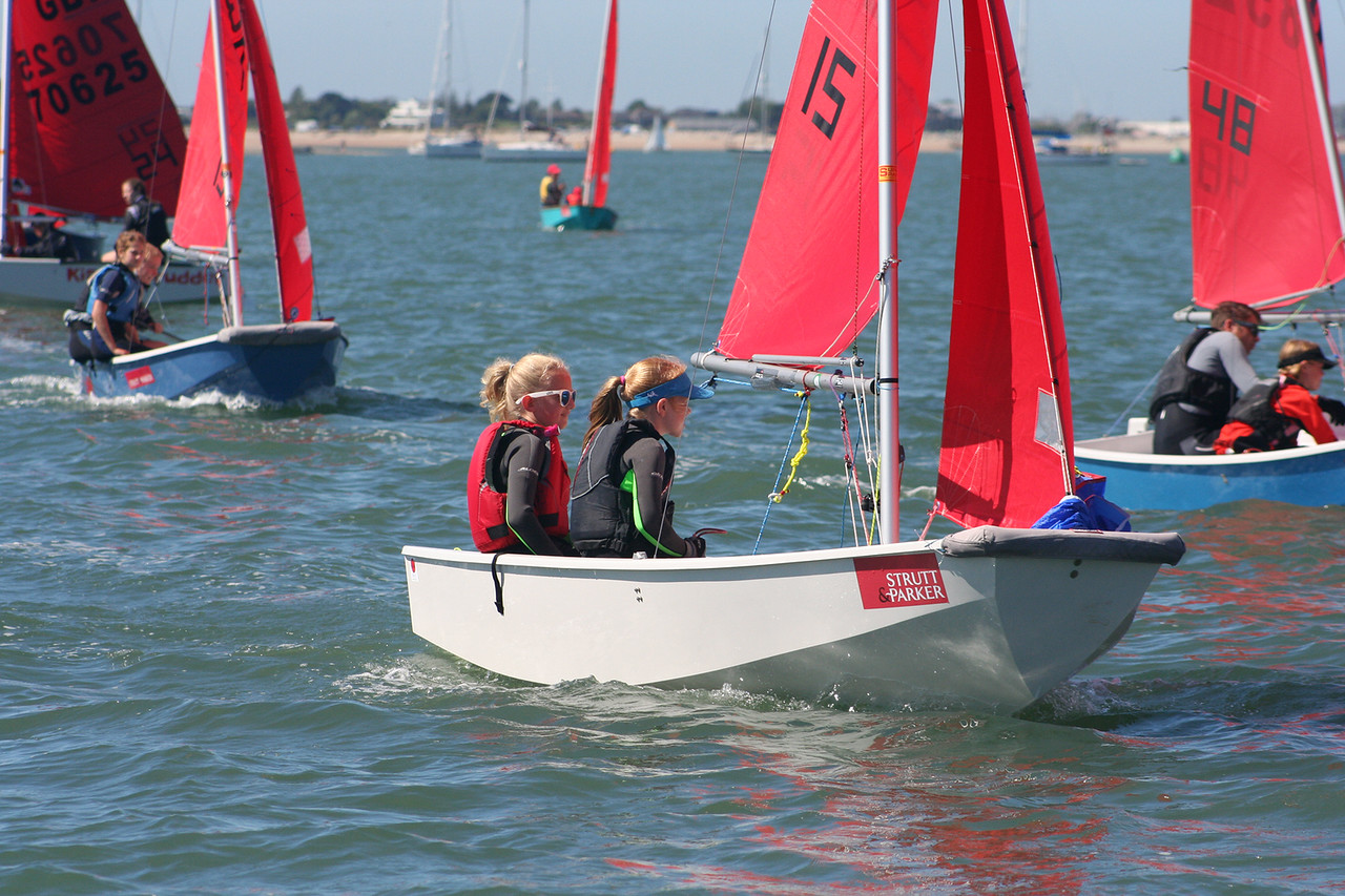 Two girls racing a GRP Mirror dinghy to windward