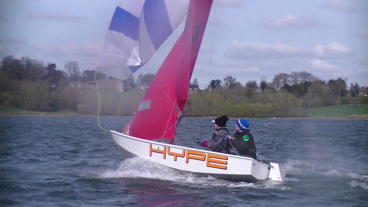 A Mirror dinghy flying a spinnaker in a strong wind