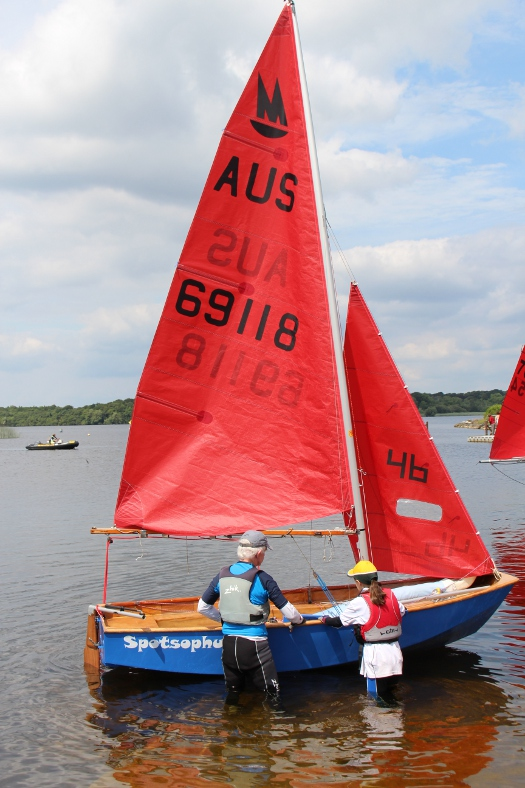 A blue wooden Mirror dinghy with AUS national letters launching