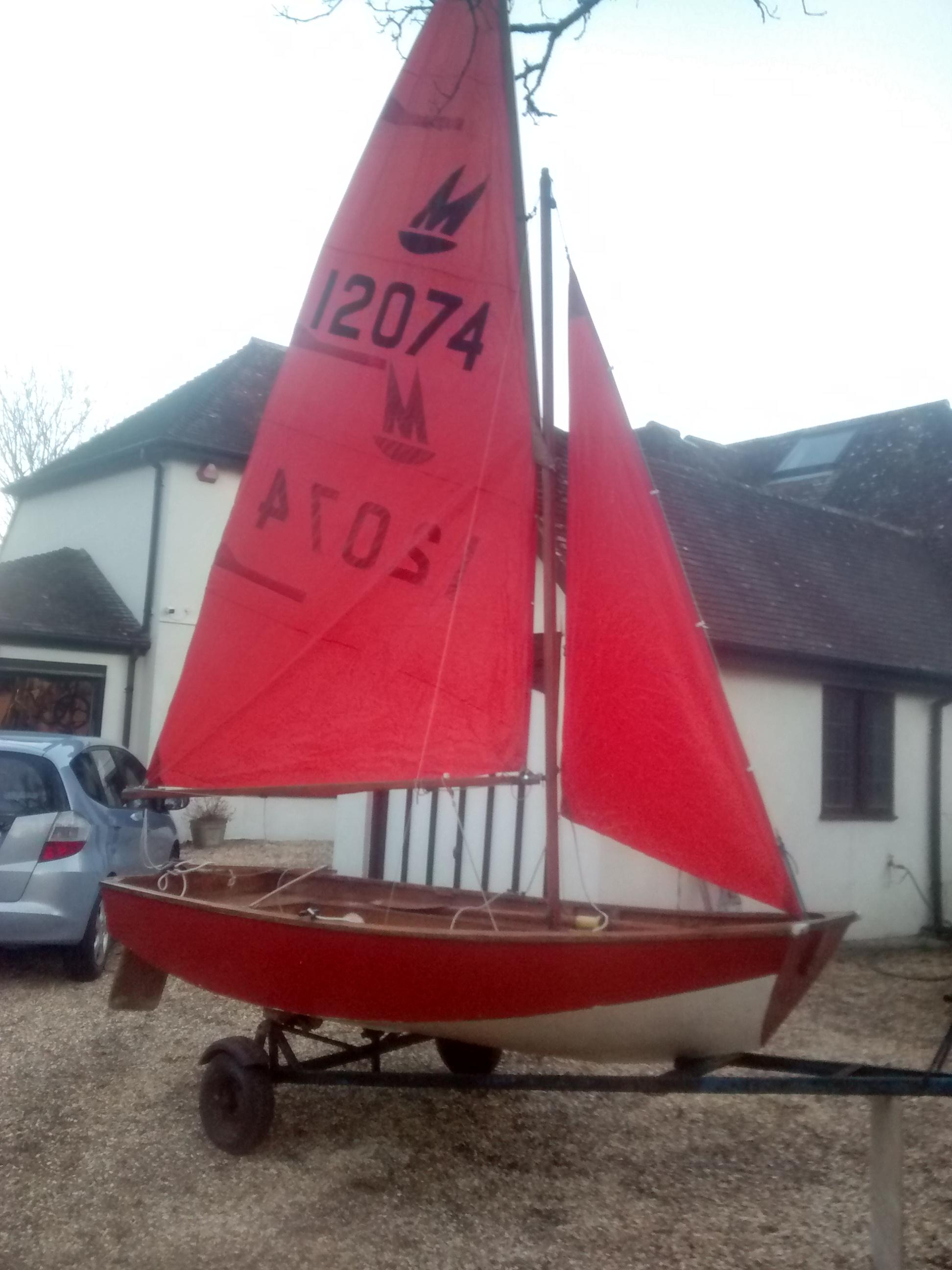 A red wooden Mirror dinghy rigged in a driveway