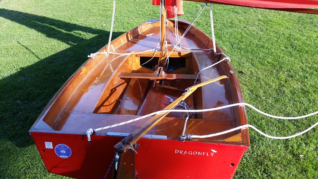 A red wooden Mirror dinghy rigged up in a grass dinghy park