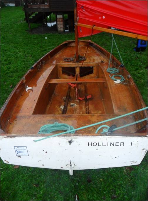 A white Mirror dinghy rigged up in a grassy dinghy park on a misty day