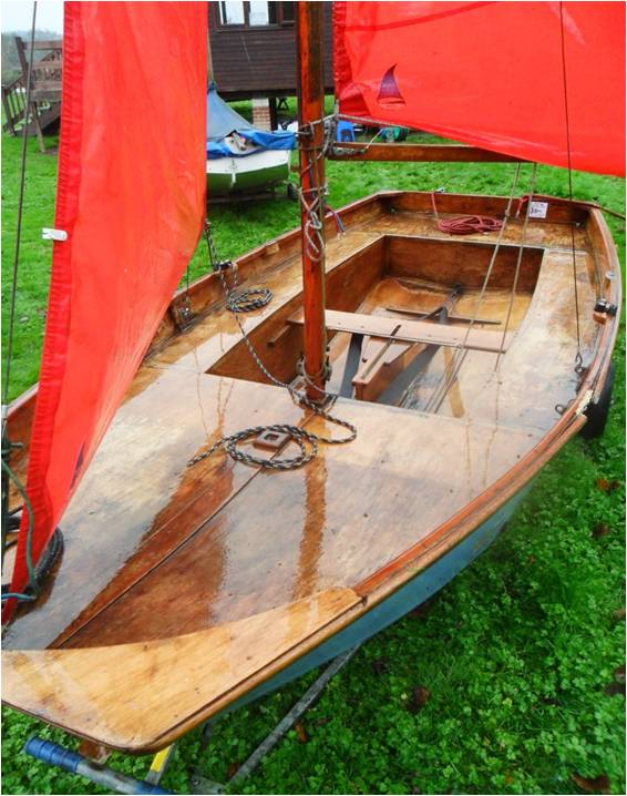 A blue Mirror dinghy rigged in a grass dinghy park on a misty day