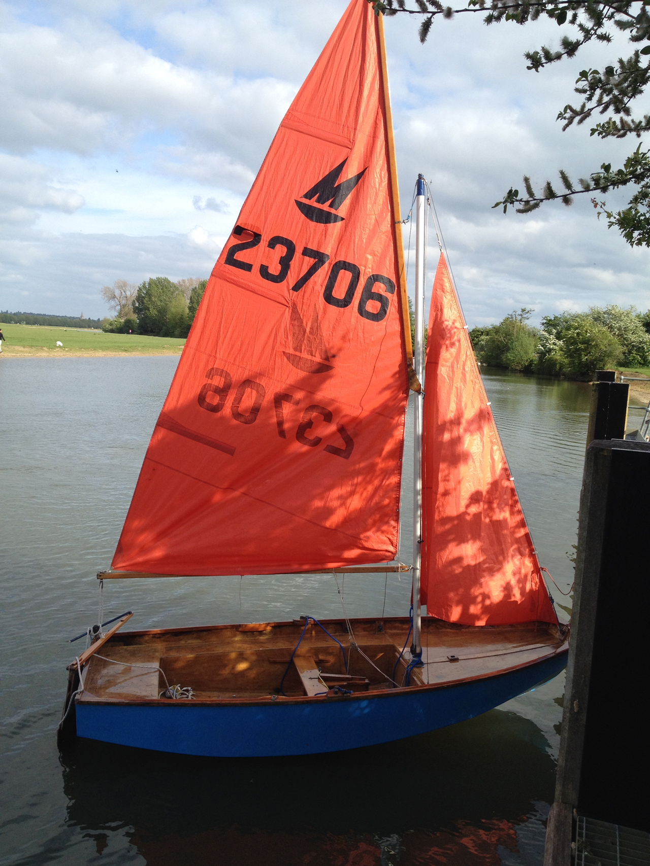 Blue wooden Mirror dinghy rigged up on the river at Oxford