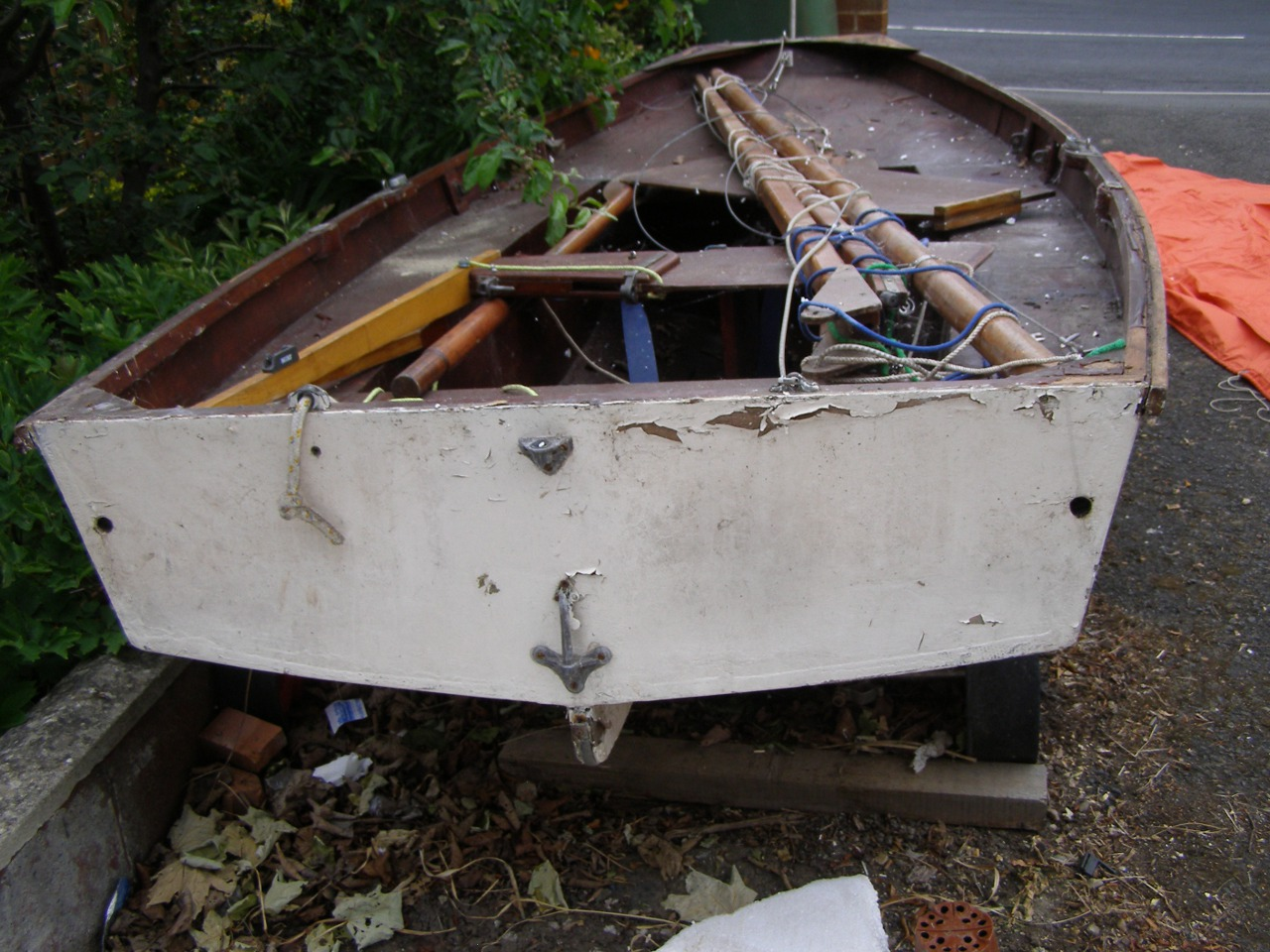 A white wooden Mirror dinghy in terrible condition with paint and varnish peeling