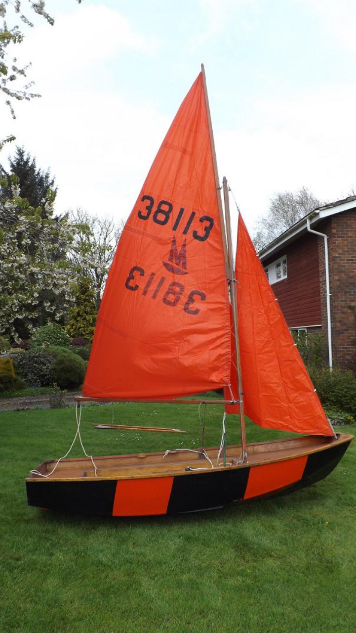A red and black wooden Mirror dinghy rigged on a lawn