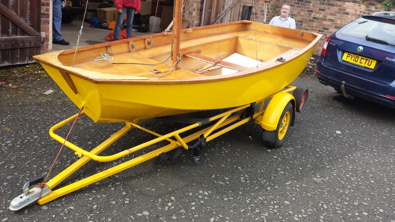 A yellow wooden Mirror dinghy on a matching yellow trolley & trailer