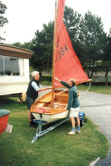 A Mirror dinghy being rigged by two gentlemen on a campsite