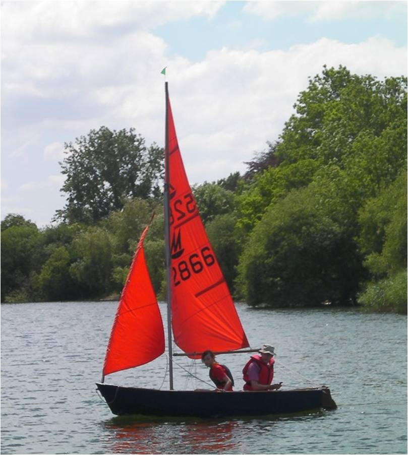 A blue wooden Mirror dinghy sailing on a lake