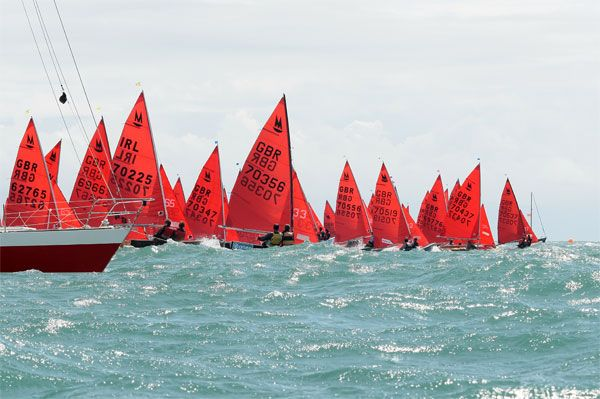 A fleet of Mirror Dinghies starting in very windy conditions in a big sea