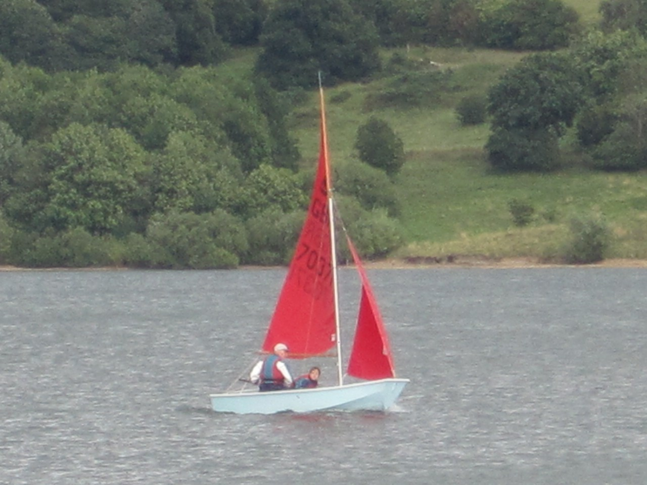 A light blue Mirror dinghy sailing on a lake with trees in the background