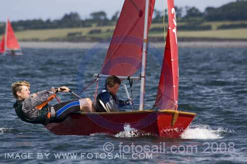Red wooden Mirror dinghy being raced to windward