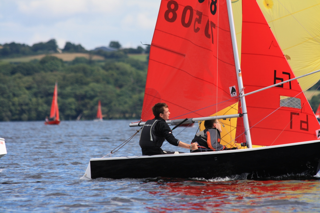 A black GRP Mirror dinghy racing in a light wind