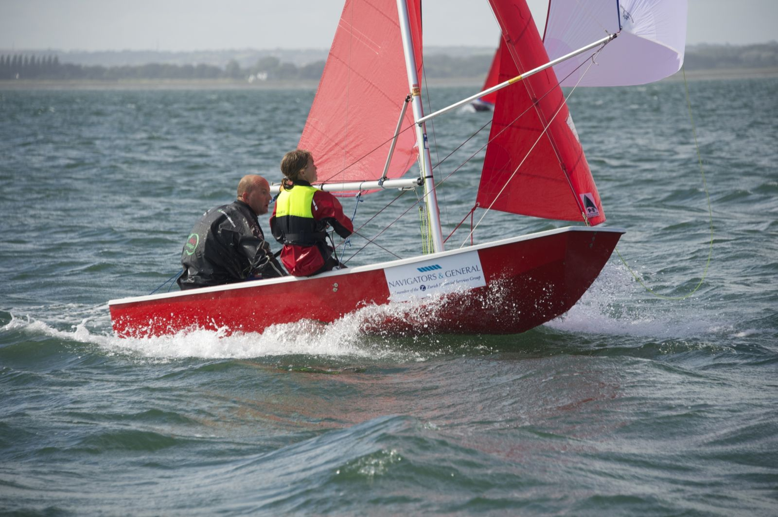 A red GRP Mirror dinghy with spinnaker racing on a reach