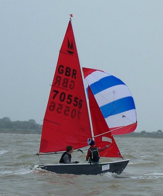 Grey Mirror dinghy racing with blue & white spinnaker on a grey day