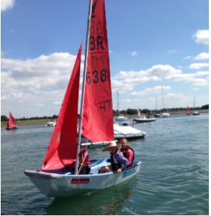 A GRP Mirror dinghy sailed by three people