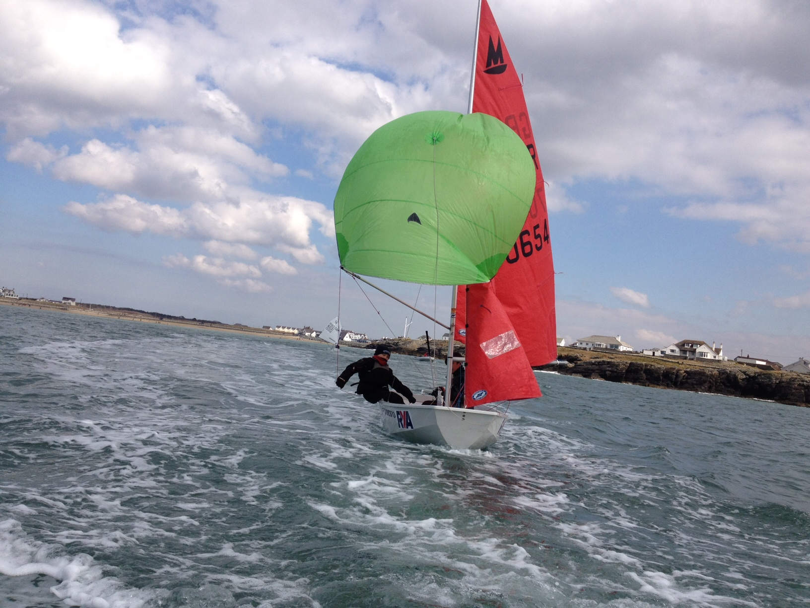A white GRP Mirror dinghy sailing with green spinnaker on an estuary