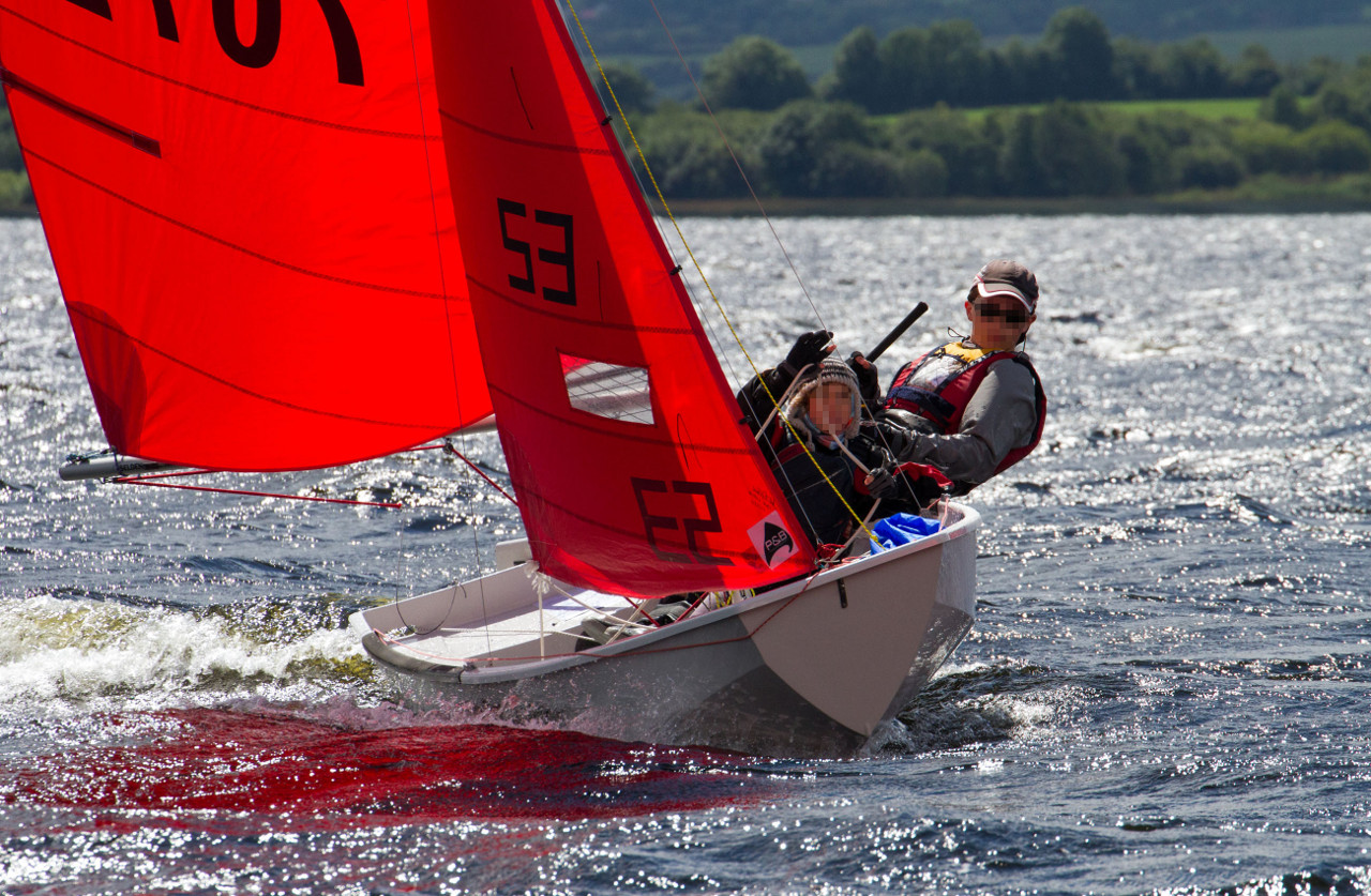 A white GRP Mirror Dinghy sailing on a reach