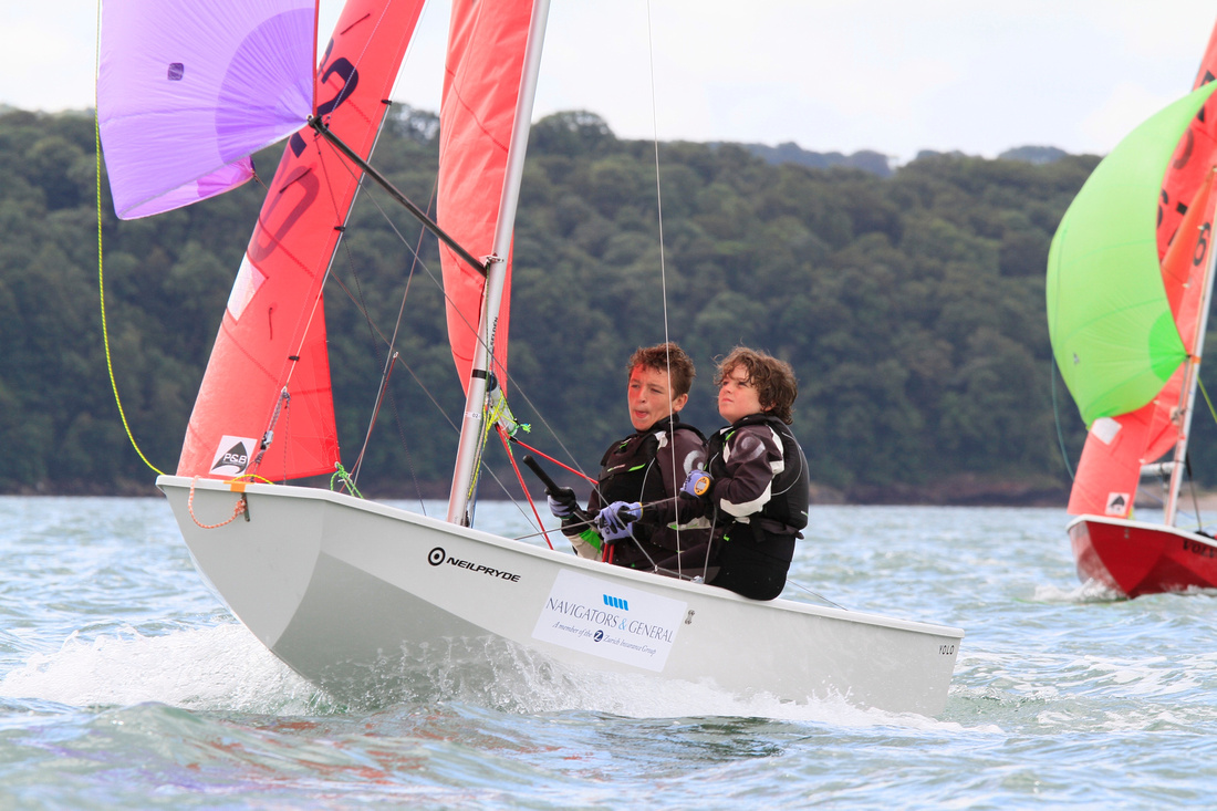 A white GRP Mirror racing with spinnaker flying