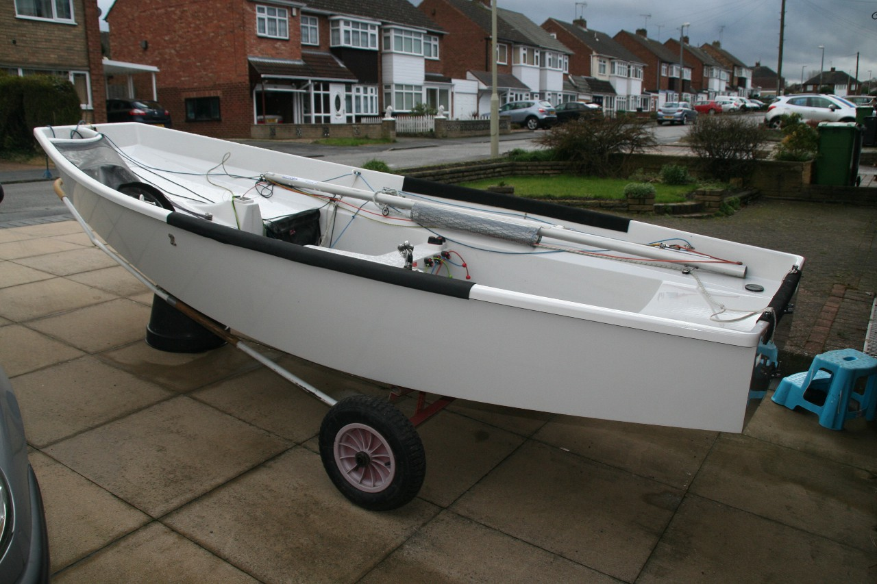 A white GRP Mirror dinghy on a driveway