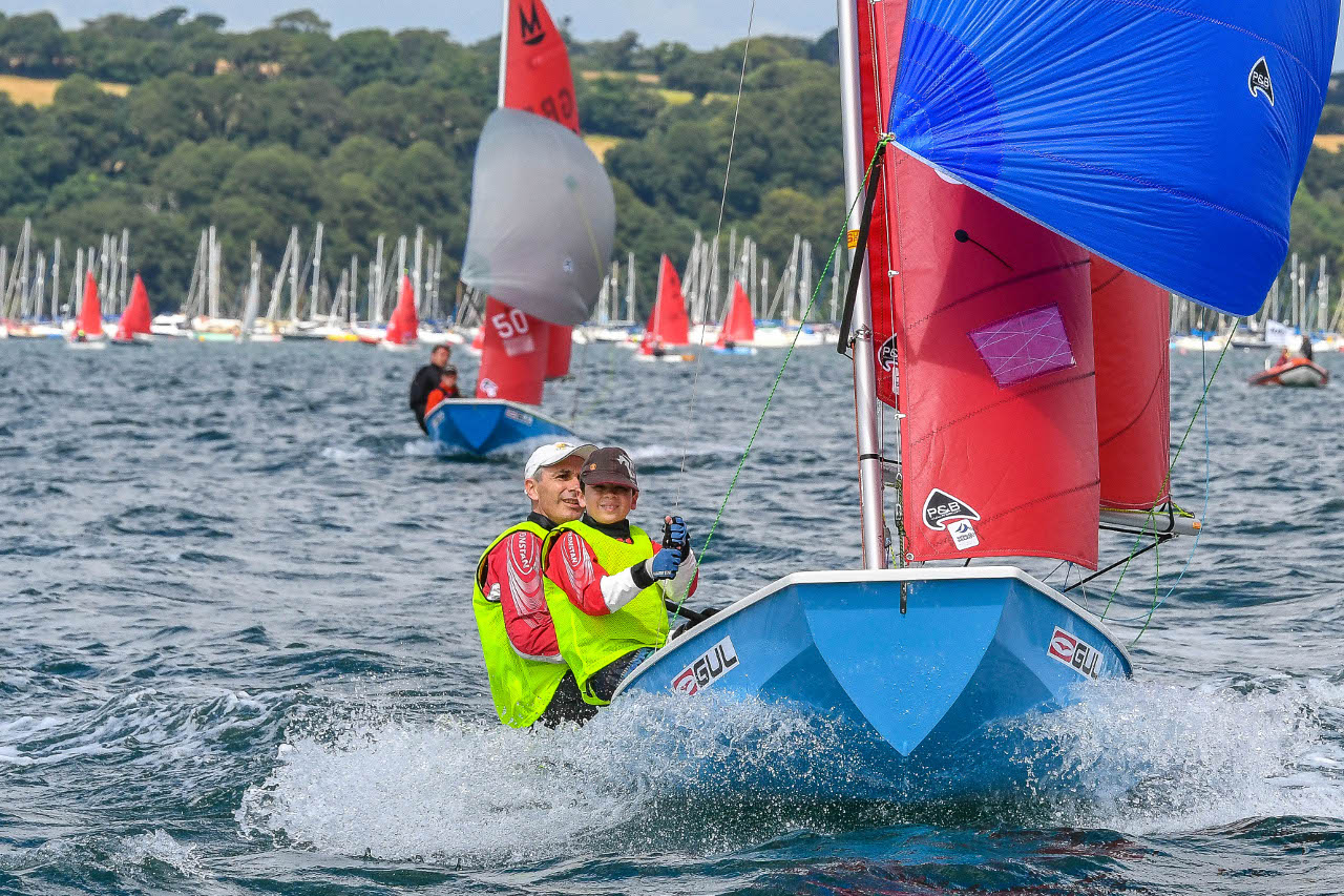 A blue GRP Mirror dinghy with spinnaker flying
