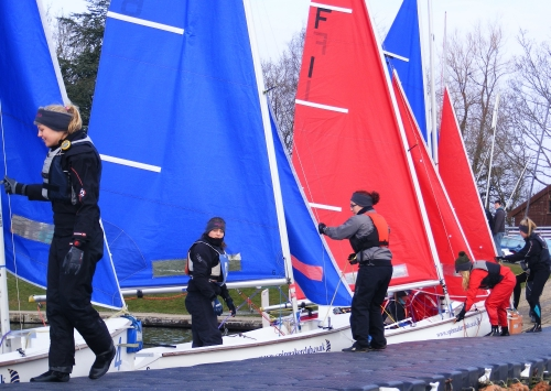 Ladies team racing helms & crews climbing into red or blue Fireflys with matching sails - nice !