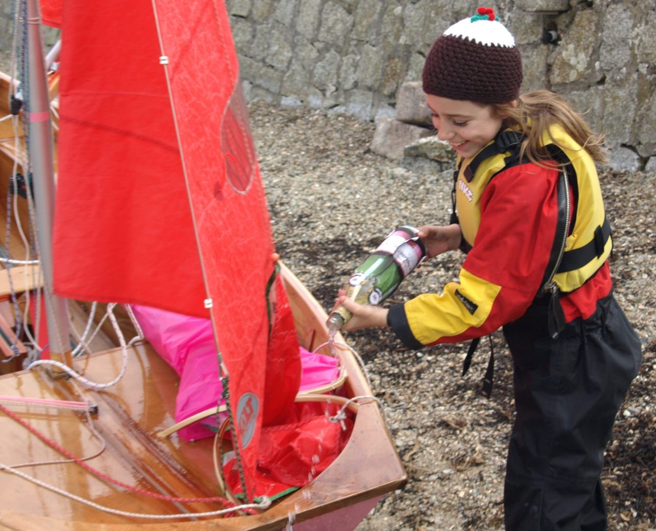 A girl pouring champgne over the bow of her pink Mirror dinghy