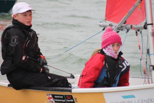 A beige GRP mirror dinghy being sailed in the winter
