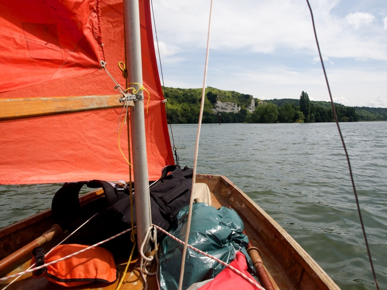 The river Seine in France viewed from the cockpit of a Mirror dinghy under sail