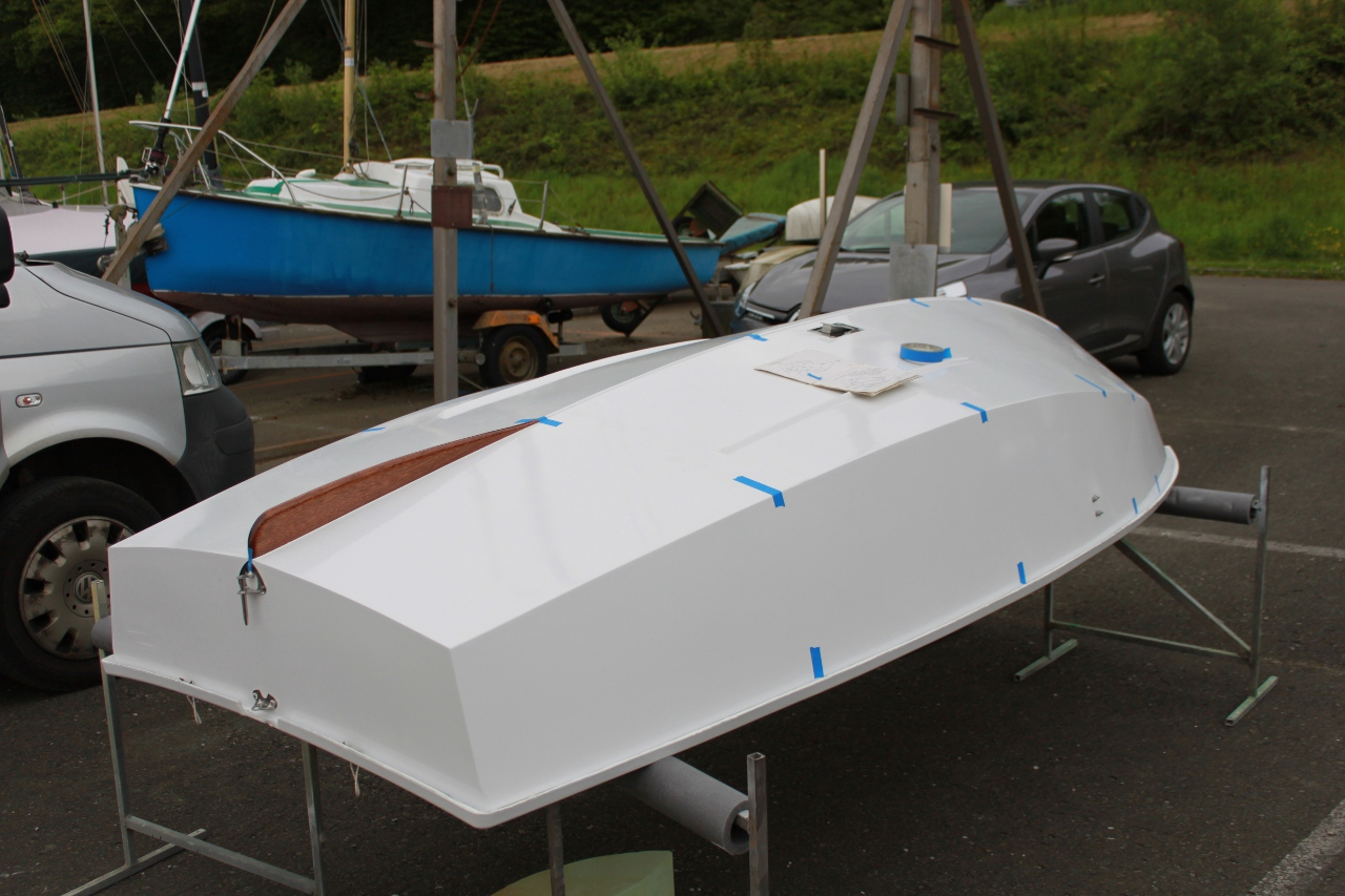 A GRP Mirror dinghy hull upside down on stands being measured with blue masking tape marking the hull stations