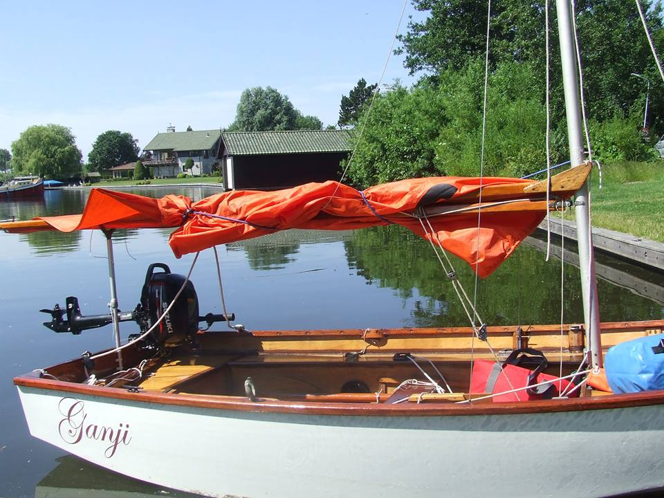 A Mirror dinghy with sails lowered, but boom held up by a boom crutch